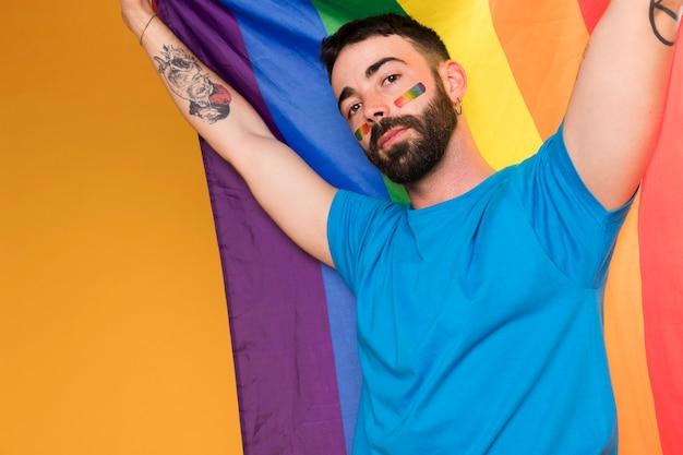 Mann mit lgbt-regenbogen auf gesicht mit mehrfarbiger flagge