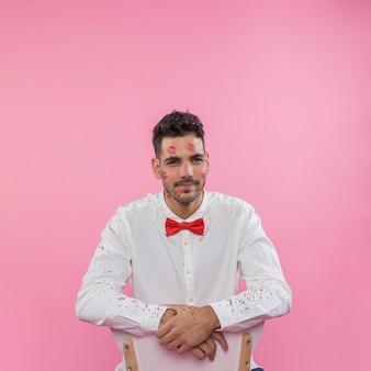 Mann mit lippenstiftkusskennzeichen auf gesicht