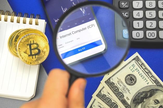 Mann mit lupe und internet computer icp kryptowährung auf handybildschirm, geschäfts- und finanzhintergrundfoto