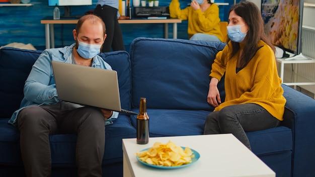 Mann mit maske, der der frau, die im wohnzimmer sitzt, einen neuen film auf dem laptop zeigt und soziale distanzierung gegen die coronavirus-pandemie hält, verhindert die ausbreitung von viren. menschen, die während des covid-19-ausbruchs kontakte knüpfen