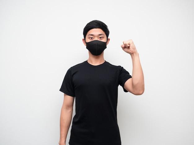 Mann mit maske selbstbewusst zeigt eine faust nach oben und schaut auf den weißen hintergrund der kamera