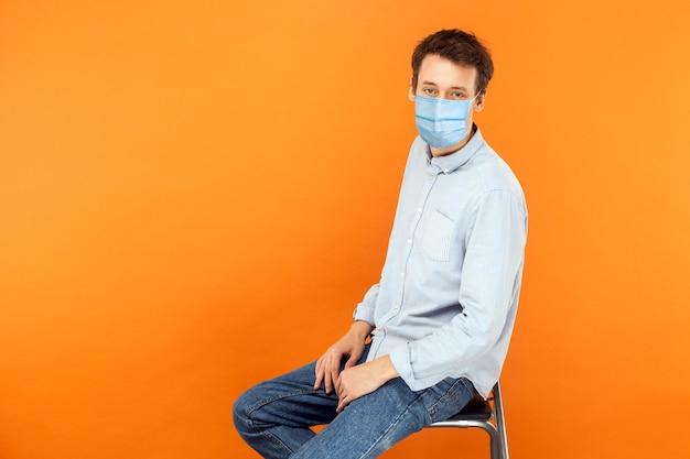 Mann mit maske sitzt und schaut in die kamera mit ernsthaftem gesichtsgesundheits- und medizinkonzept