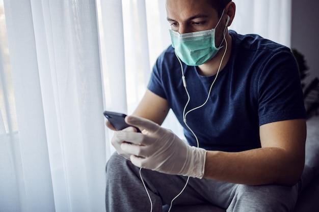 Mann mit maske und handschuhen, die musik hören und am smartphone tippen. bleib zuhause. weltpandemie, coronavirus.