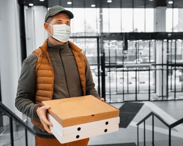 Mann mit maskenhaltepaket ausliefern