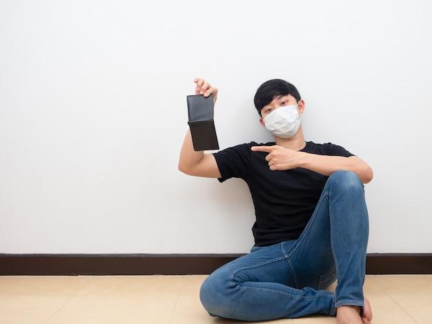 Mann mit maskenpunkt an leerer brieftasche in der hand, der auf dem weißen wandhintergrund des bodens sitzt