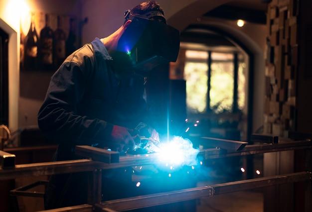 Mann mit maskenschweißen von metall im atelier