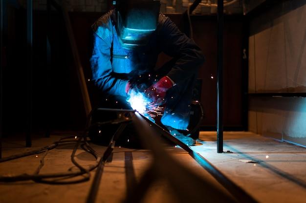 Mann mit maskenschweißen von metall im atelier Premium Fotos