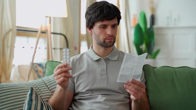 Mann mit medikamenten liest die anweisungen für die medizinische verwendung des arzneimittels.