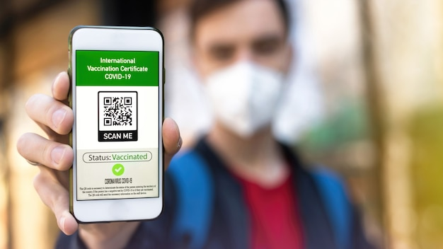 Mann mit medizinischer maske, der einen internationalen impfausweis covid-19-qr-code auf dem smartphone zeigt