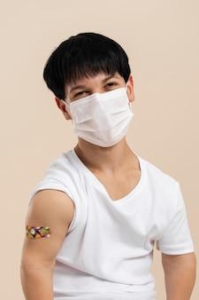 Mann mit medizinischer maske, der nach dem impfstoff arm mit aufkleber zeigt