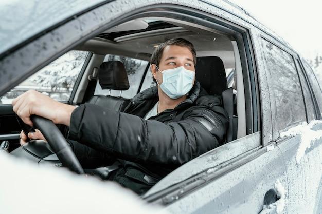Mann mit medizinischer maske, die auto für einen roadtrip fährt