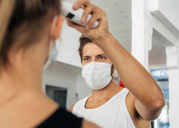 Mann mit medizinischer maske im fitnessstudio, das die temperatur der frau prüft