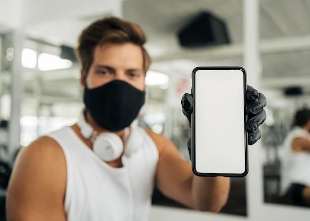 Mann mit medizinischer maske und kopfhörern an der turnhalle, die smartphone zeigt