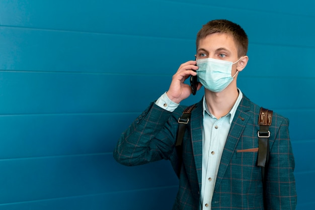 Mann mit medizinischer maske und rucksack, der am telefon spricht