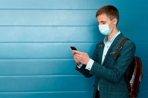 Mann mit medizinischer maske und rucksack unter verwendung des smartphones
