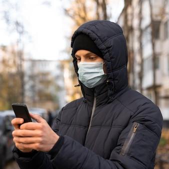 Mann mit medizinischer maske unter verwendung des smartphones im freien
