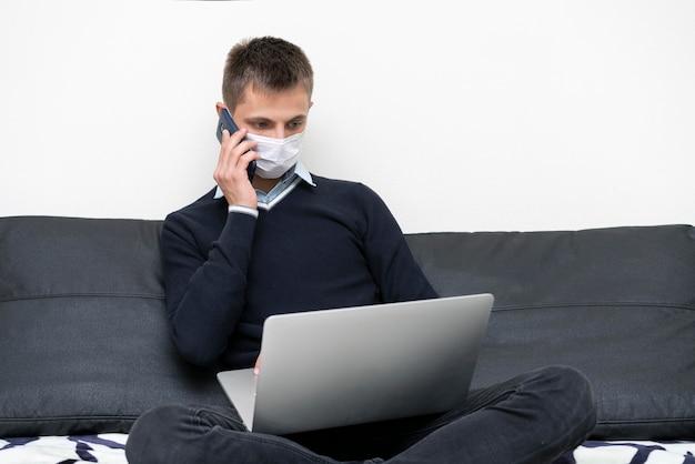 Mann mit medizinischer maske unter verwendung von laptop und smartphone