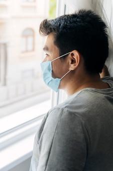 Mann mit medizinischer maske zu hause während der pandemie, die durch das fenster schaut