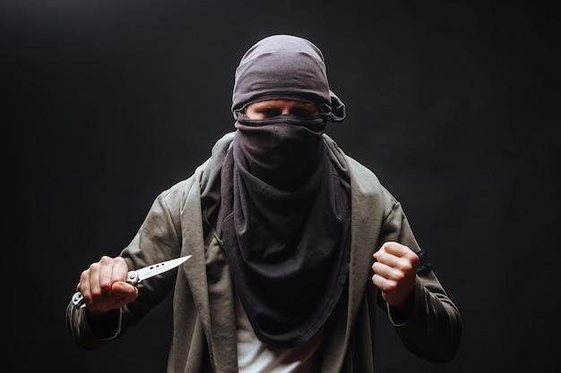 Mann mit messer und maske auf dunklem hintergrund
