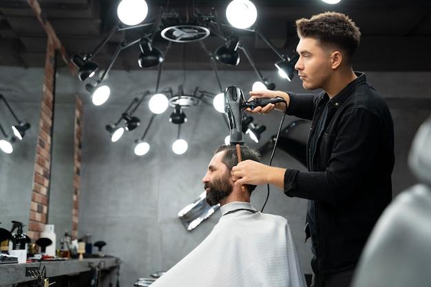 Mann mit mittlerem schuss bekommt haarschnitt