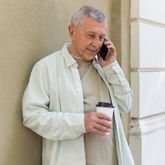 Mann mit mittlerem schuss, der am telefon telefoniert