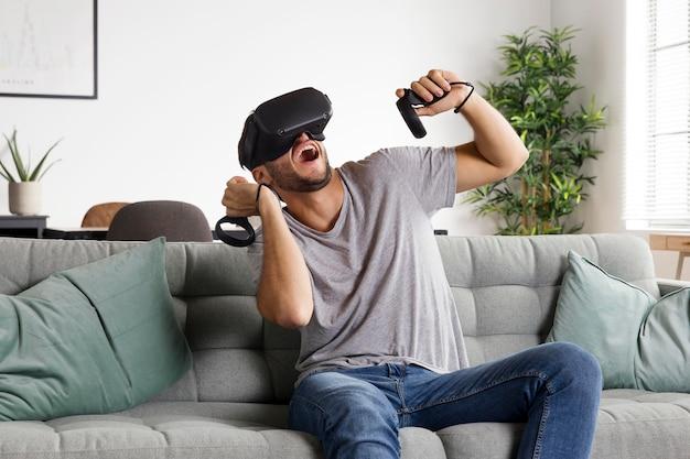 Mann mit mittlerem schuss, der auf der couch spielt