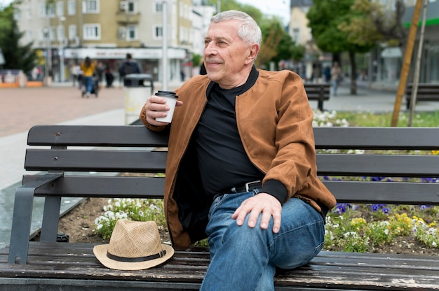Mann mit mittlerem schuss, der auf einer bank sitzt