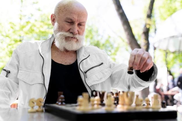 Mann mit mittlerem schuss, der draußen schach spielt