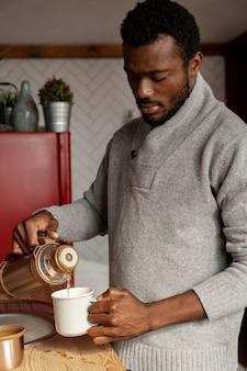 Mann mit mittlerem schuss, der heißen kaffee einschenkt