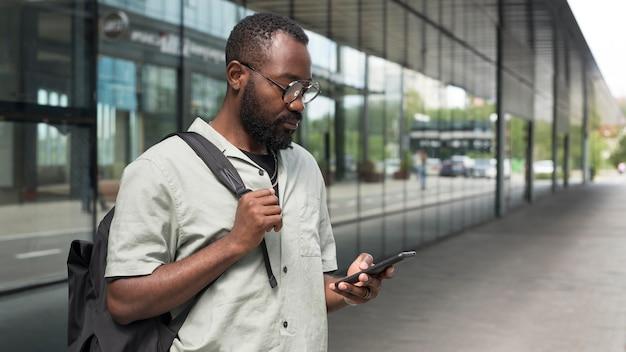 Mann mit mittlerem schuss, der telefon hält