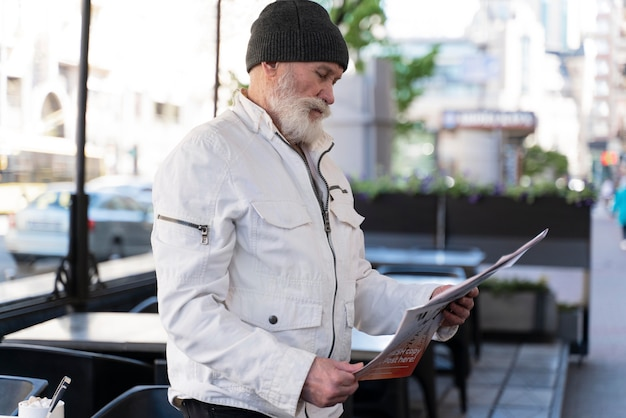 Mann mit mittlerem schuss, der zeitung liest