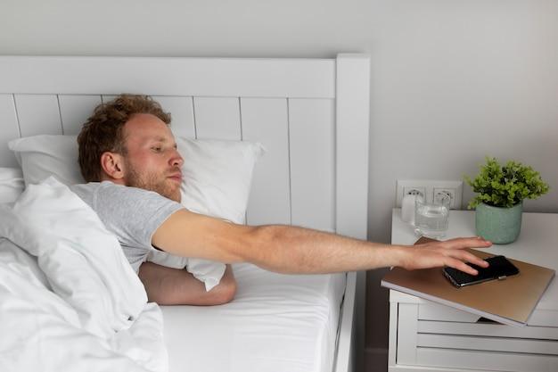 Mann mit mittlerem schuss schaltet den alarm aus