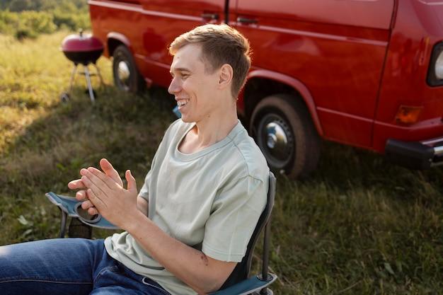 Mann mit mittlerer aufnahme, der auf stuhl sitzt