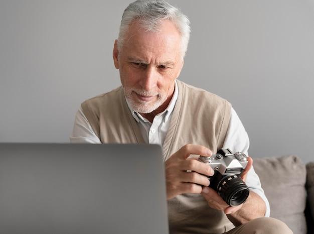 Mann mit mittlerer aufnahme, der eine fotokamera hält