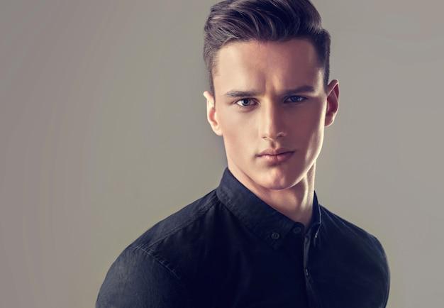 Mann mit modischem haarschnitt und schwarzem pullover