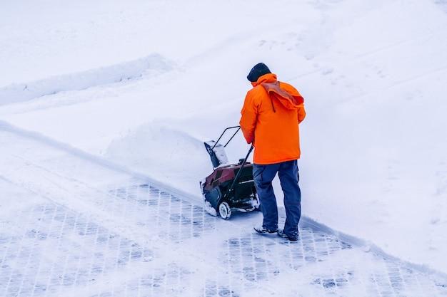 Mann mit motorisierter bahnantrieb schneefräse räumt schnee, eine schneefräse auf einem schneebedeckten straßendetail. motormaschine zum entfernen von nassem, schwerem schnee. schneefräsenausrüstung.