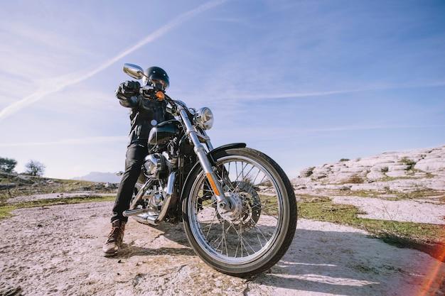 Mann mit motorrad auf felsen
