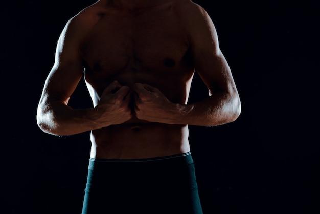 Mann mit muskulösen bauchmuskeln abgeschnittene ansicht des dunklen hintergrunds des fitnessstudios. foto in hoher qualität