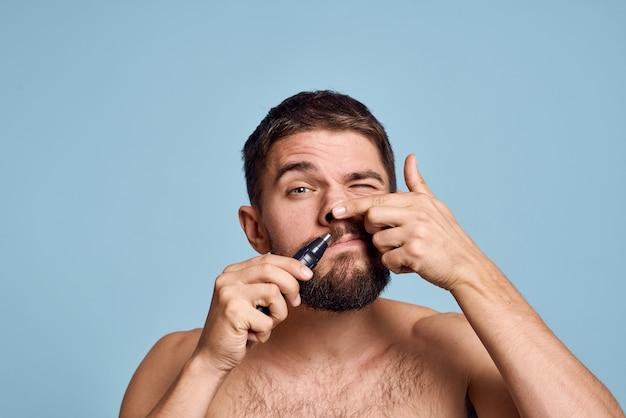 Mann mit nackten schultern entfernt nase haarhygiene pflege blau