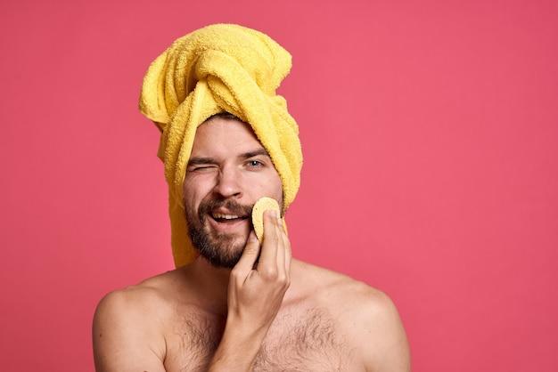 Mann mit nackten schultern in einem gelben handtuch auf seinem kopf schwamm saubere hautpflege rosa