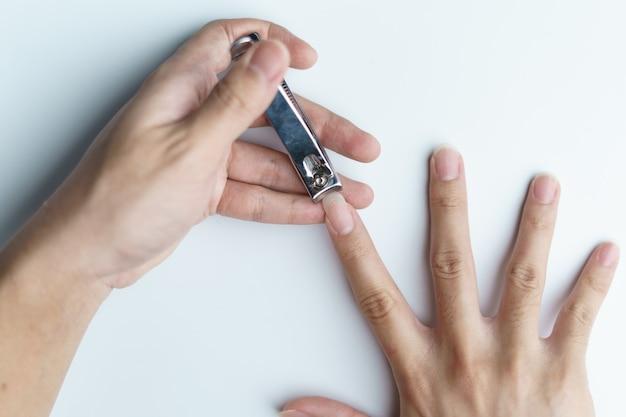 Mann mit nagelknipser schneidet ihre fingernägel