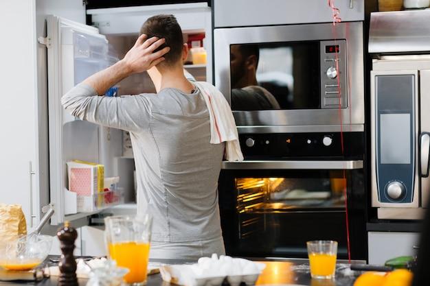 Mann mit offenem kühlschrank