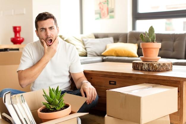 Mann mit offenem mund und weit geöffneten augen und hand am kinn, der sich unangenehm geschockt fühlt und sagt, was oder wow