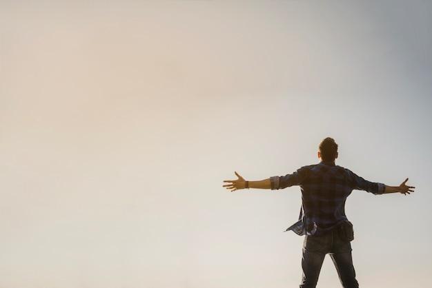 Mann mit offenen armen blick auf den himmel