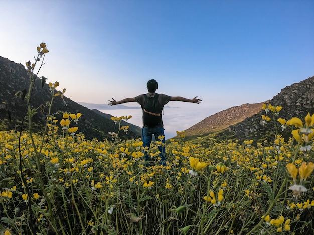 Mann mit offenen armen steht über blumenlandschaft eines bergigen tals