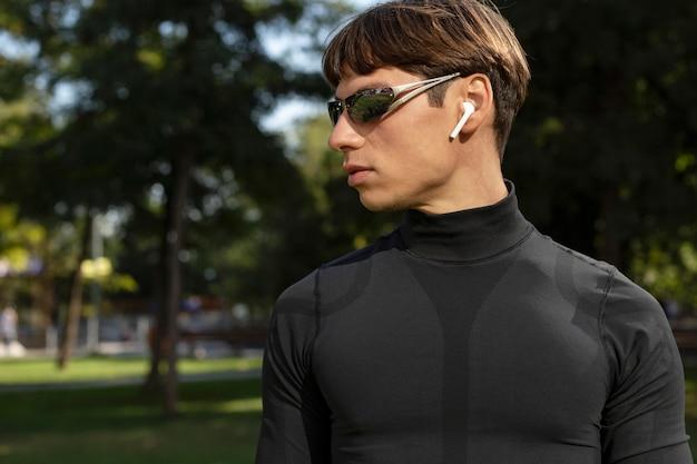 Mann mit ohrhörern und sonnenbrille, die draußen arbeiten
