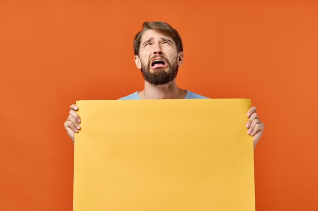 Mann mit orange blatt papier poster marketing isoliert hintergrund.