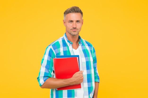 Mann mit ordner gelbem hintergrund. geschäftsmann hält buch für notizen. kerl hat notizblock zum schreiben. hübscher schul- oder universitätslehrer. erwachsener mann student mit notebooks. inspiriert, hart zu arbeiten.