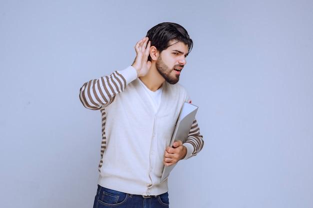 Mann mit ordner zeigt auf sein ohr, da er nicht hören kann.