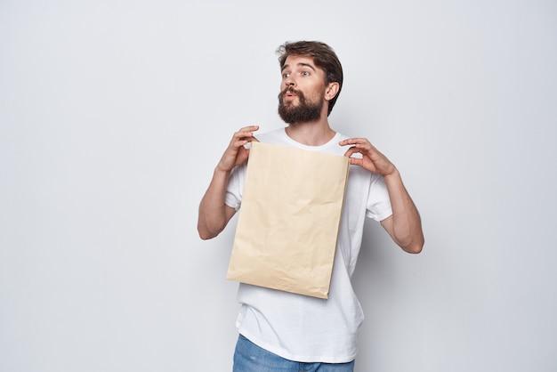 Mann mit papiertüte in den händen modellieren einkaufsgefühle heller hintergrund
